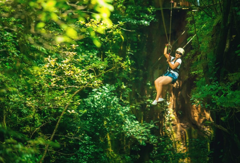 Woman enjoying the thrill of zip lining through the jungle on women's tour to Costa Rica.